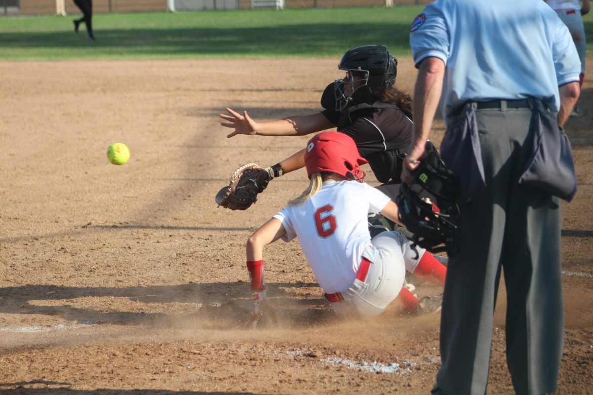 """Jessie Hopper, sophomore, slides into home base at a varsity softball game. """"[Softball] gives me a good excuse to really bond with people from other classes, not just people in my own grade. It really broadens my horizons, it distracts me from school and all the pressure."""""""