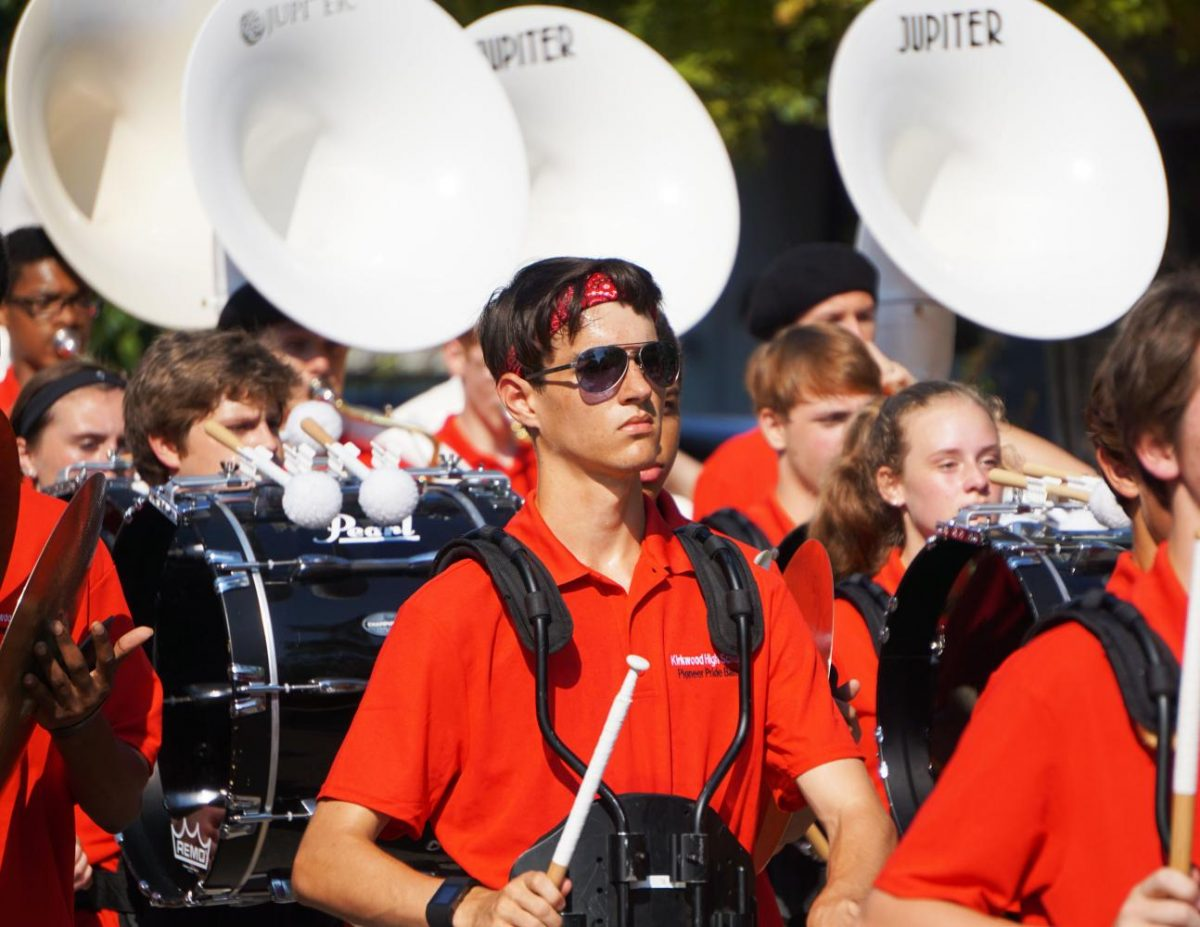 "Parading down toward the field in a sea of red, Atticus Bute, junior, marches and drums along with the rest of the Kirkwood Pioneer Pride Band. The band marches from the parking lot to the field at the start of every home football game. ""I love the community. Everyone loves playing music and has fun playing it, and everyone is always smiling."""