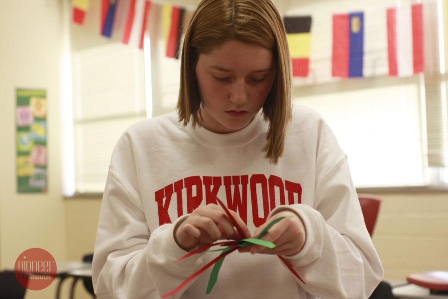 """Claire Zickel, sophomore, focuses on the christmas star she is making during a German Club meeting on Dec 7, """"[German club] is really fun and we get to do cool stuff, it's a really chill environment."""""""