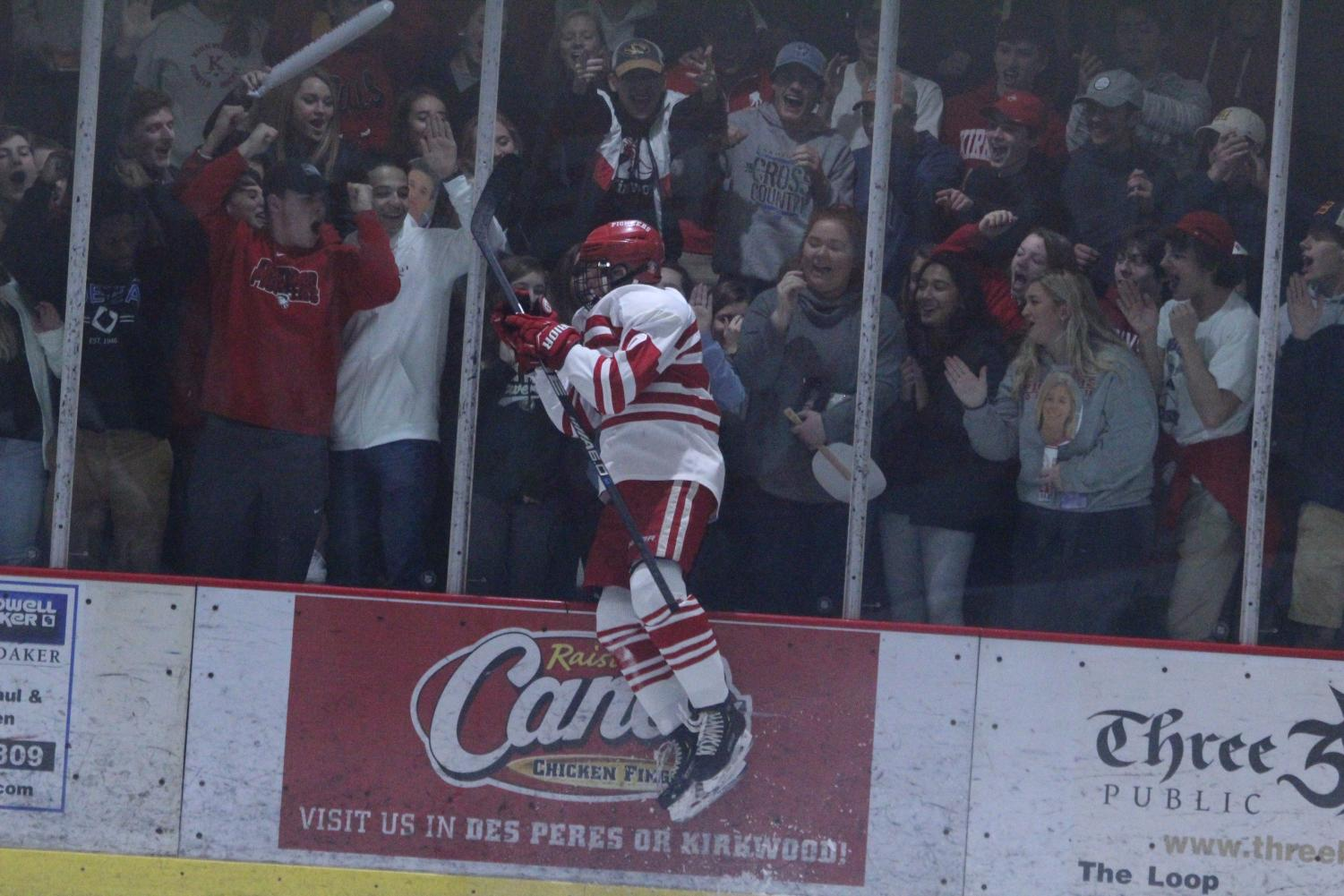 Seamus+Campbell%2C+junior%2C+celebrates+his+goal+by+jumping+into+the+glass+on+senior+night+against+Vianney+High+School+Jan.+15.+