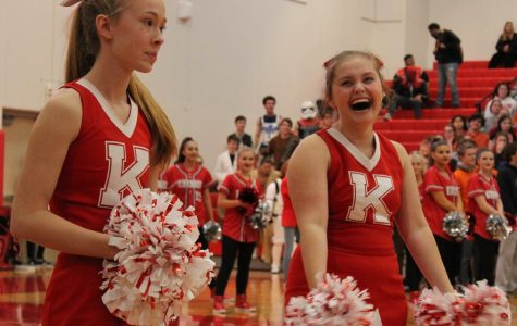 Watching as students and teachers walk in the gym, Izzy Schwent and Maddie Bromfman, sophomores, cheer at the Turkey Day Pep Rally. Nov 30.