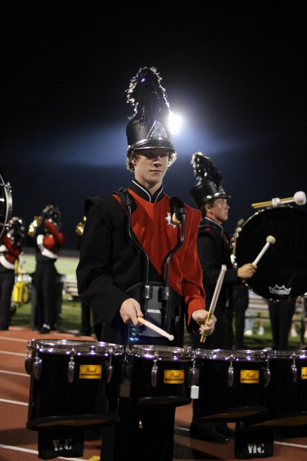 Focussing on his rhythms, Nick Kelsch, senior, plays the tenors at the football game Sept. 7.