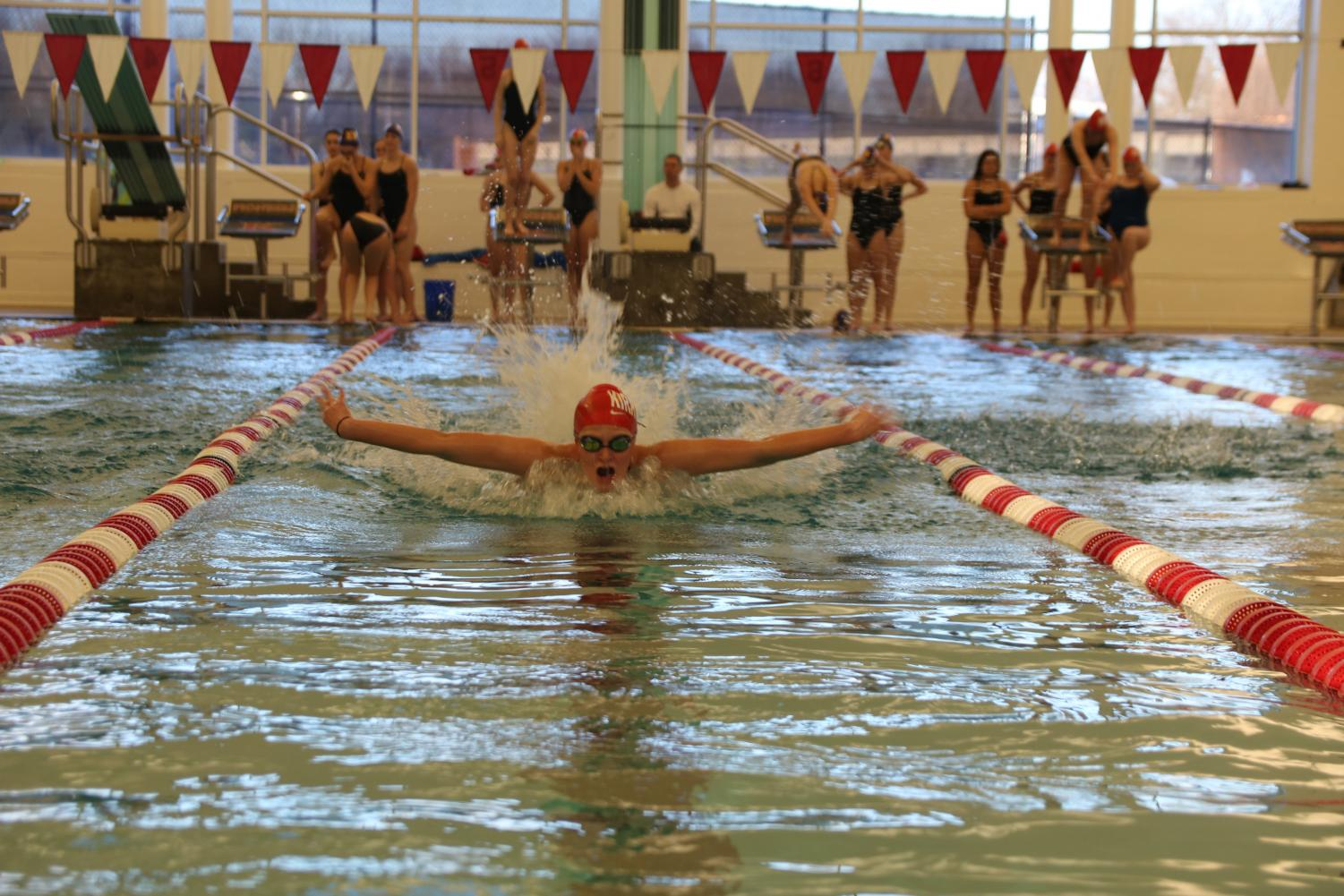 At+the+start+of+the+Senior+Night+swim+meet%2C+Molly+Sheridan%2C+senior%2C+pushes+up+out+of+the+water+to+take+a+breath+as+she+swims+fly.+Her+arms+stretching+across+the+lane+as+the+late+afternoon+sun+shines+through+the+windows+of+the+Walker+Natatorium+Jan.+24.