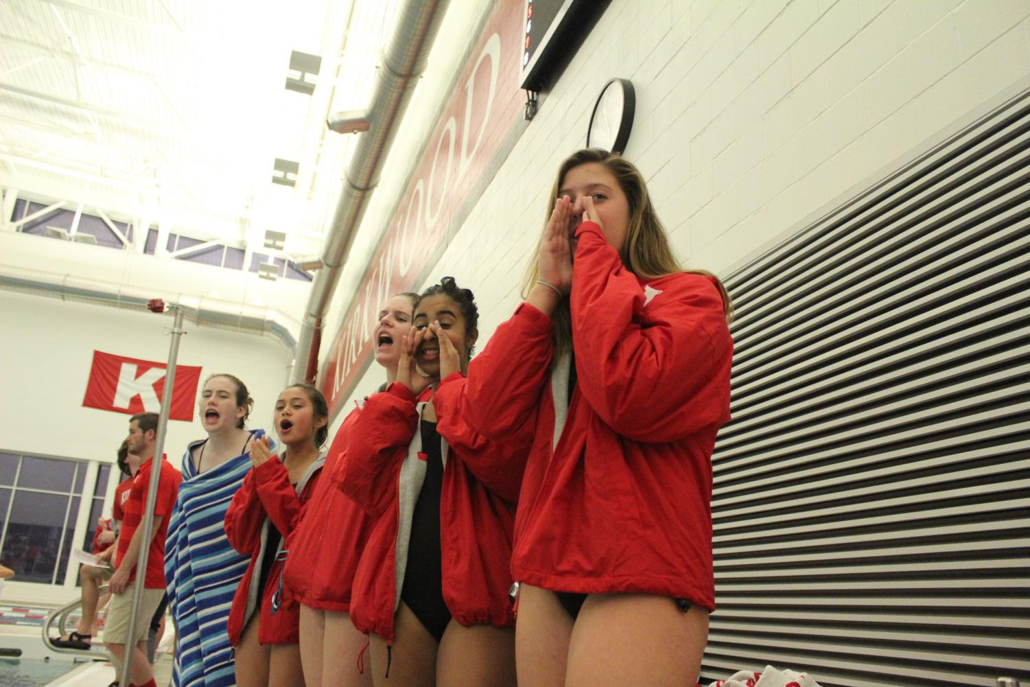 Cheering+for+their+teammates%2C+members+of+the+girls+swim+and+dive+team+stand+on+the+sidelines+during+the+Kirkwood+v.+Webster+swim+meet+Nov.+27.%0A
