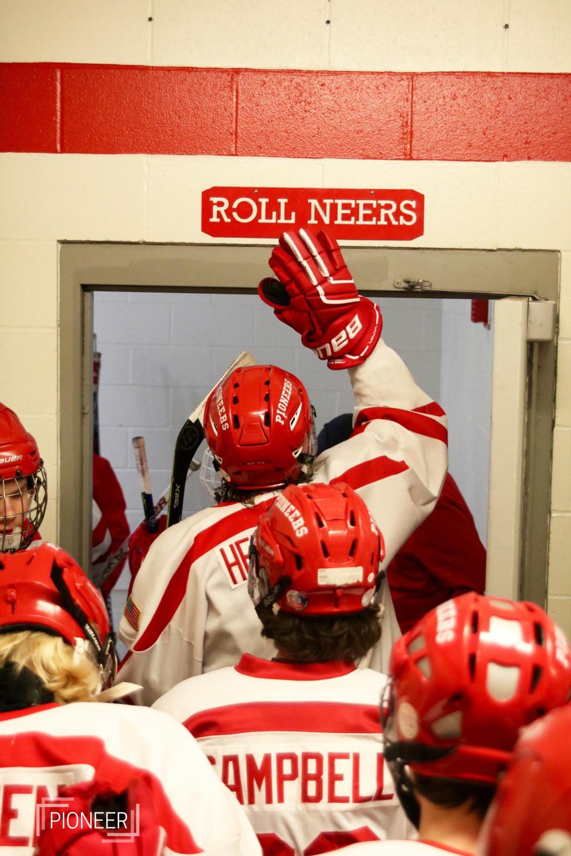 Leaving+the+locker+room+to+enter+the+rink%2C+Andrew+Herweck%2C+junior%2C+hits+the+rollneers+sign+above+the+door+Jan.+26