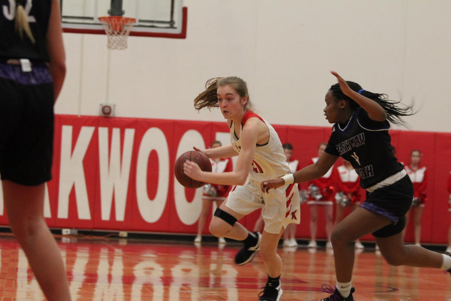 During+the+girls%E2%80%99+varsity+basketball+game%2C+Sarah+Musson%2C+sophomore%2C+drives+past+the+defender+Feb.+8.