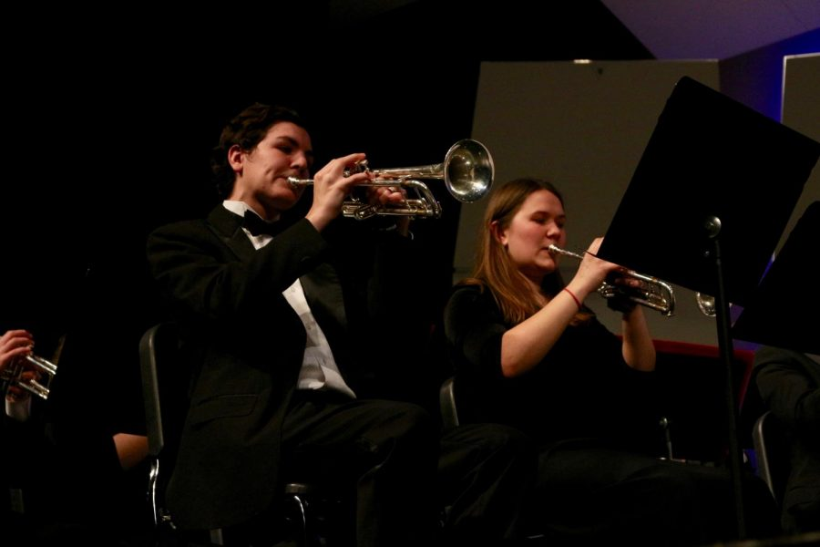 Playing the trumpets, Clark Woodruff and Grace Mennerick, juniors, perform at the band concert Feb. 28.