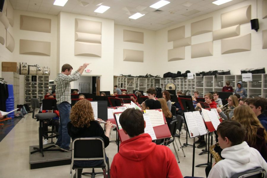 Conducting+the+Concert+Band%2C+Dr.+Bartz%2C+conductor%2C+stands+on+the+podium+Feb.+19.+