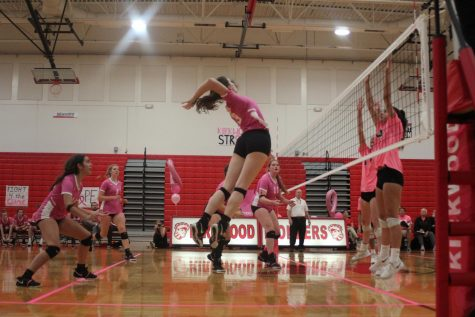 Spiking the ball, Ellie Brandon, senior, scores a point Oct. 10