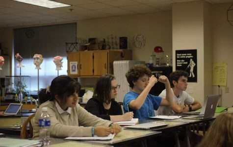 After getting a question right, Ezra Mendelson, sophomore, cheers during a lesson in Honors Chemistry Sept.18.