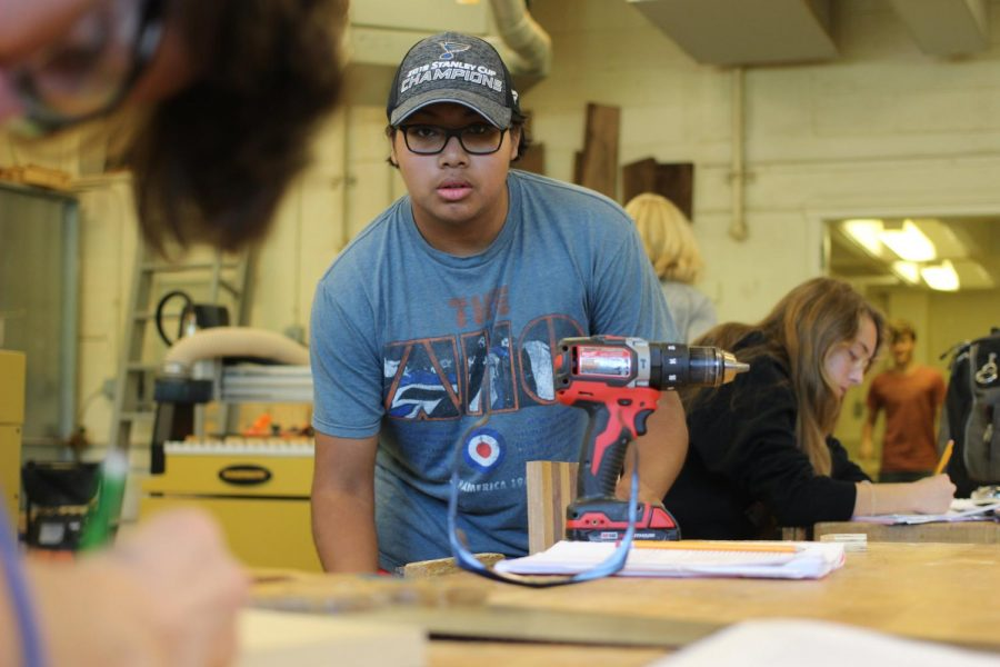 Plugging in a power tool, Scott Theerman, senior, prepares to drill a hole into his project in woodworking class Sept. 4.