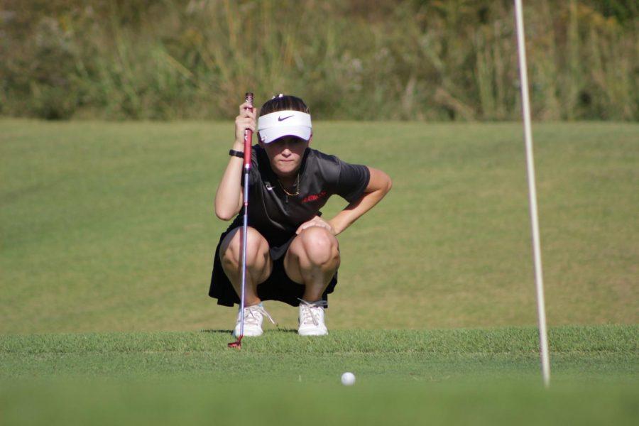 Planning her next move, Morgan Gindler, junior, keeps an eye on the ball at Aberdeen Golf club, Sept 30.