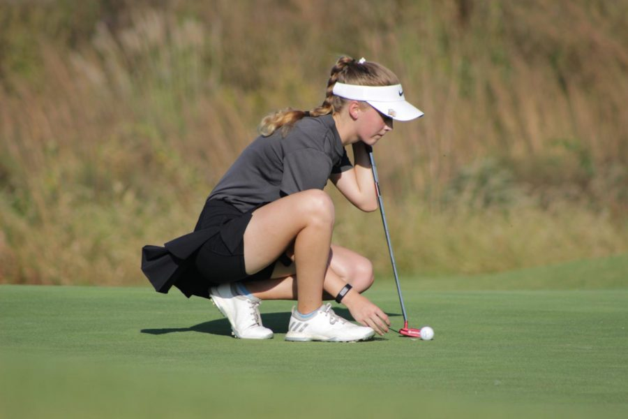 Concentrating on ball, Morgan Gindler, junior, places the ball on the green at Aberdeen Golf Club, Sept 30.