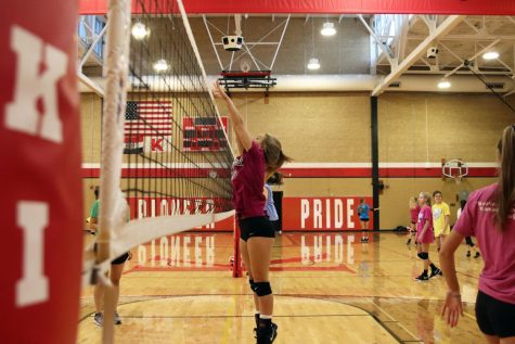 Hands outstretched, Kaylie Hinrichs, freshmen, reaches for the net during practice Sept. 24.