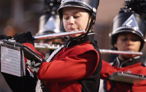 Following the music as she marches, flute player Audrey Bast performs under the lights at khs Sept 27. Hannah Banks