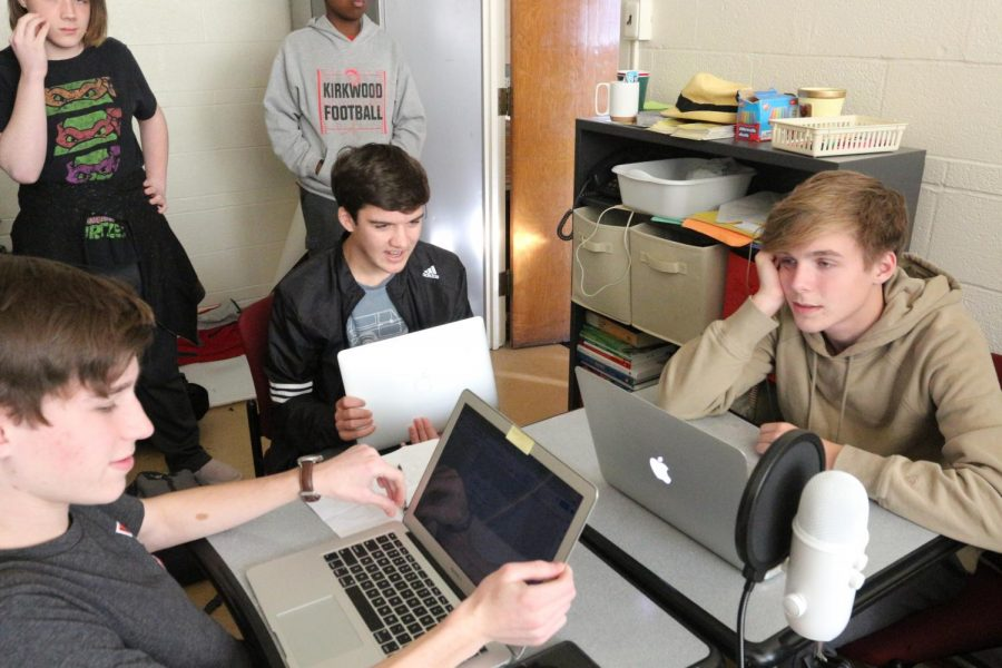 Staring at their computers, Will Bergman, Cale Owens and Ben Mobley, sophomores, discuss a podcast for class, Dec.10.