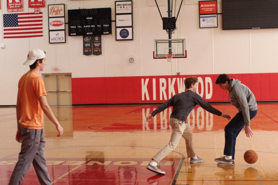 Reaching for the ball, Eddie Killeen, and Paul Goessling, seniors, play basketball in yearbook Jan. 8.