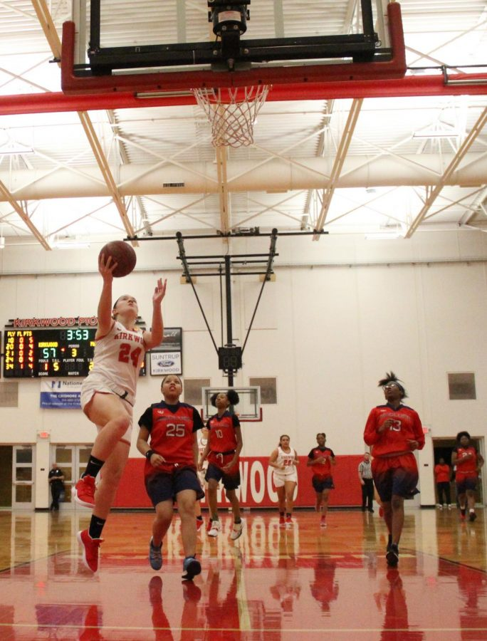 Jumping off the ground, Lauren Mills, junior, goes for a layup at a game against McCluer North Dec. 10.