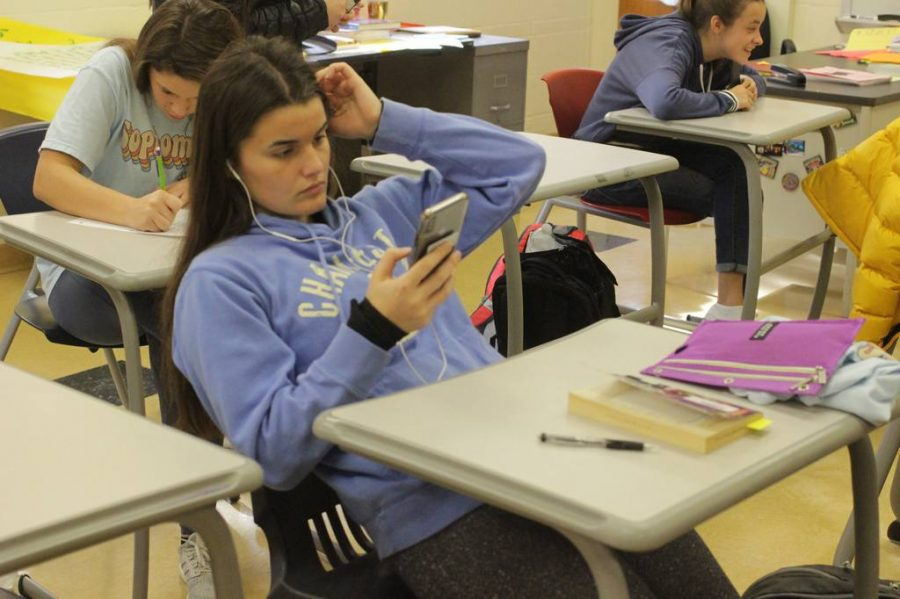 Looking at her phone on November 25, Sienna Wright, sophomore, finishes her test in spanish III and listens to music while her classmates finish testing.