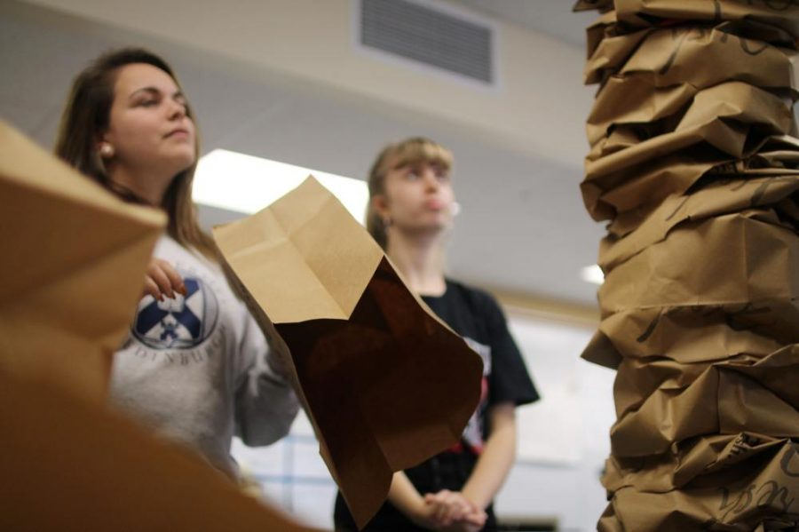 Gazing up at the progress they've made so far, sophomores Elena Sherwood and Audrey Blaine use paper bags to construct a fake tree for their Turkey Day hallway. Nov 20.