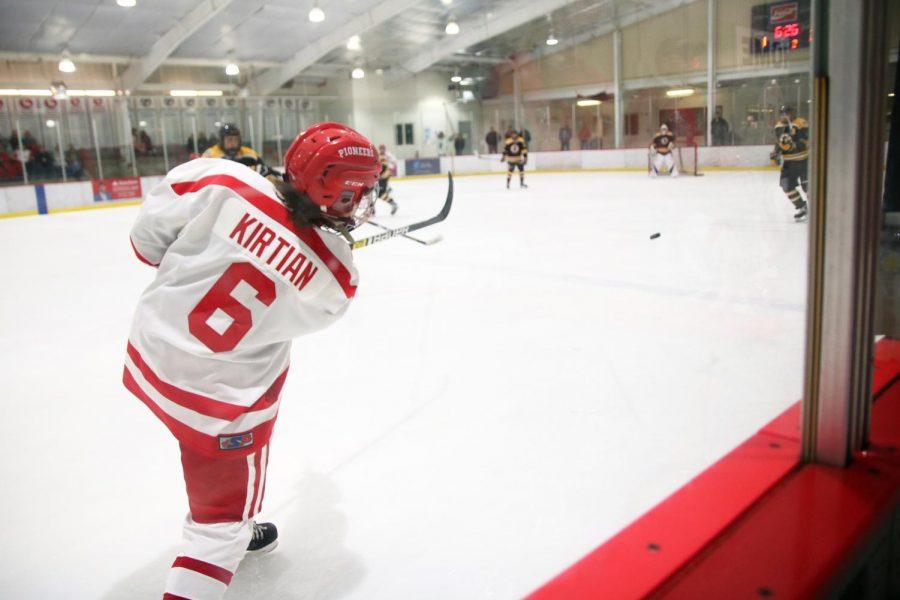 As the puck flies through the air, Max Kirtian,sophomore,  follows through on his shot during the JV hockey game against Oakville High School Jan. 7.