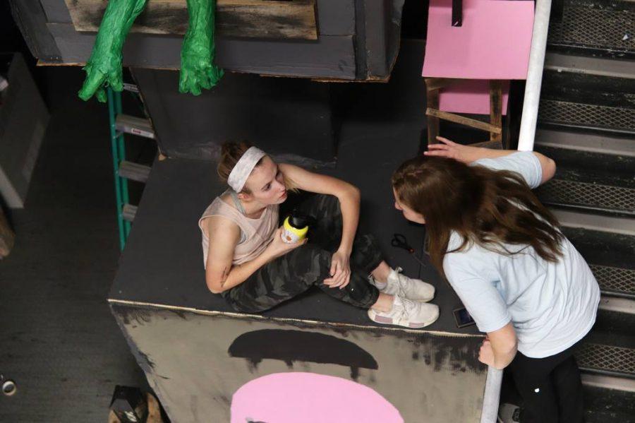 Sitting on the Once-ler's house, sophomores Bridgit Krug and Ellie Palambo take a break during hallway building Nov. 25.