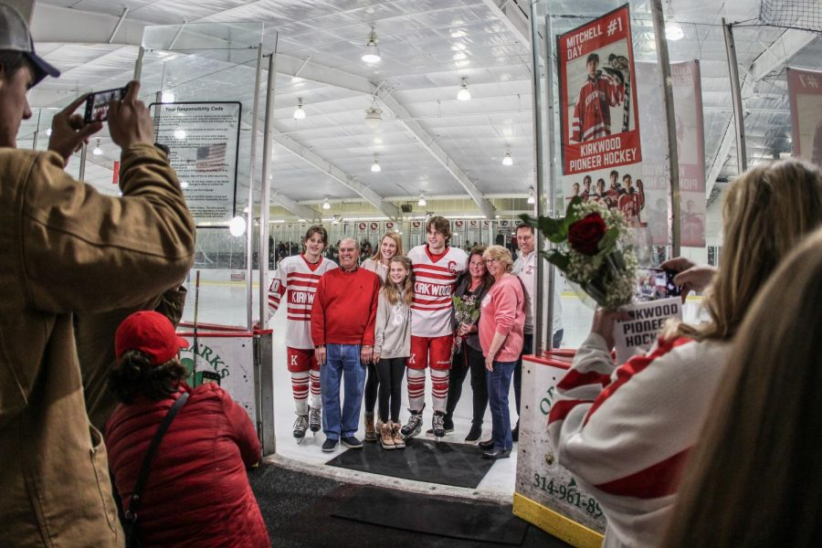 As friends and family crowd the ice rink, Andrew Herweck, senior, takes a photo with his family during senior night Jan. 11.