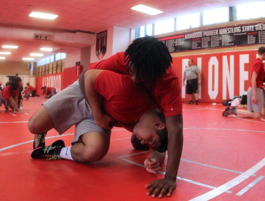 Elvis Mostek, sophomore, wrestles teammate Micah Harris, sophomore, during practice after school.