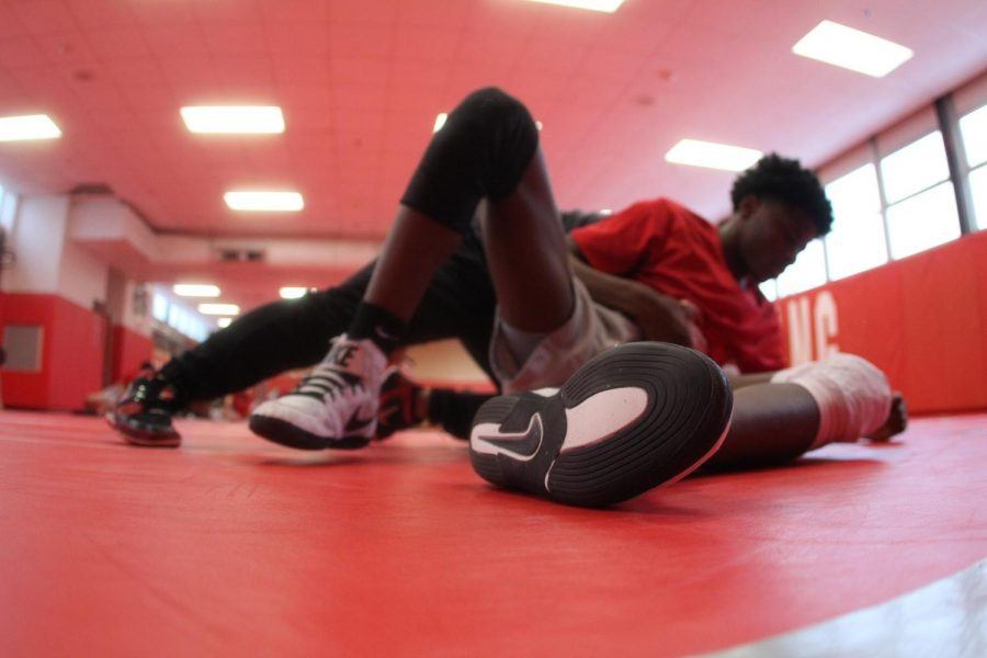 Laying down on the wrestling mat, Landry Brown, junior, practices new positions with teammate after school.