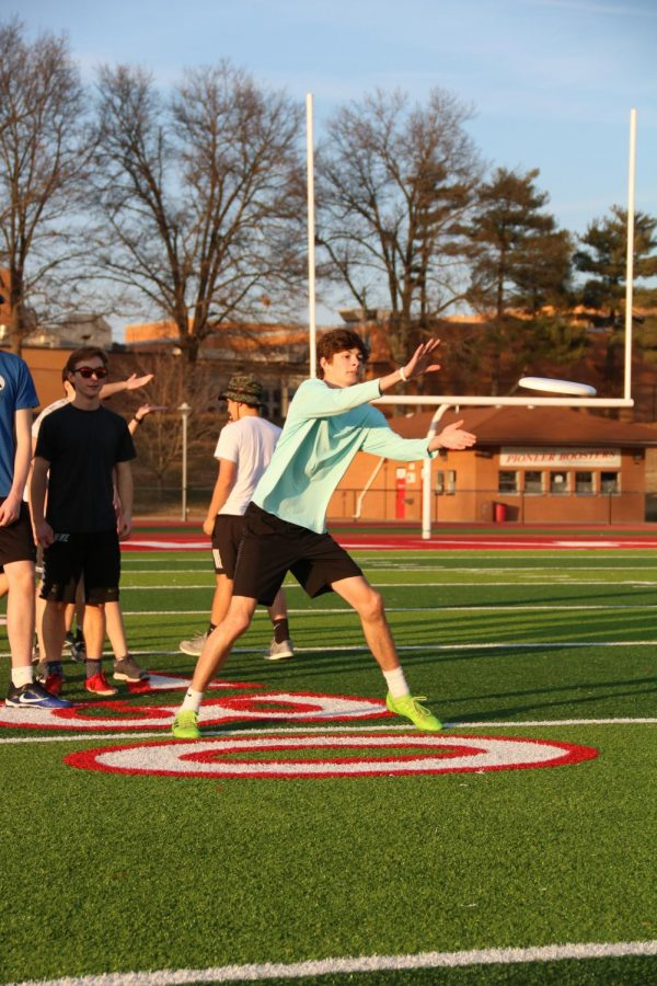 Reaching out his hands, Holden Ave, senior, catches the frisbee during the warm-up lines at ultimate frisbee practice Jan 14.