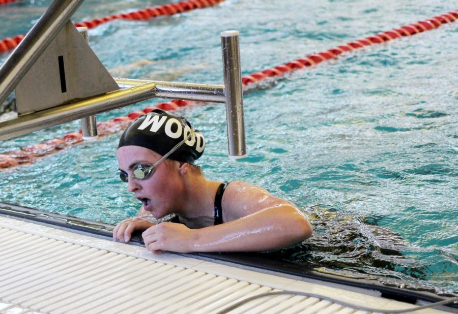 After swimming, Paige Howell, junior, catches her breath at the Kirkwood Invitational Jan. 18.