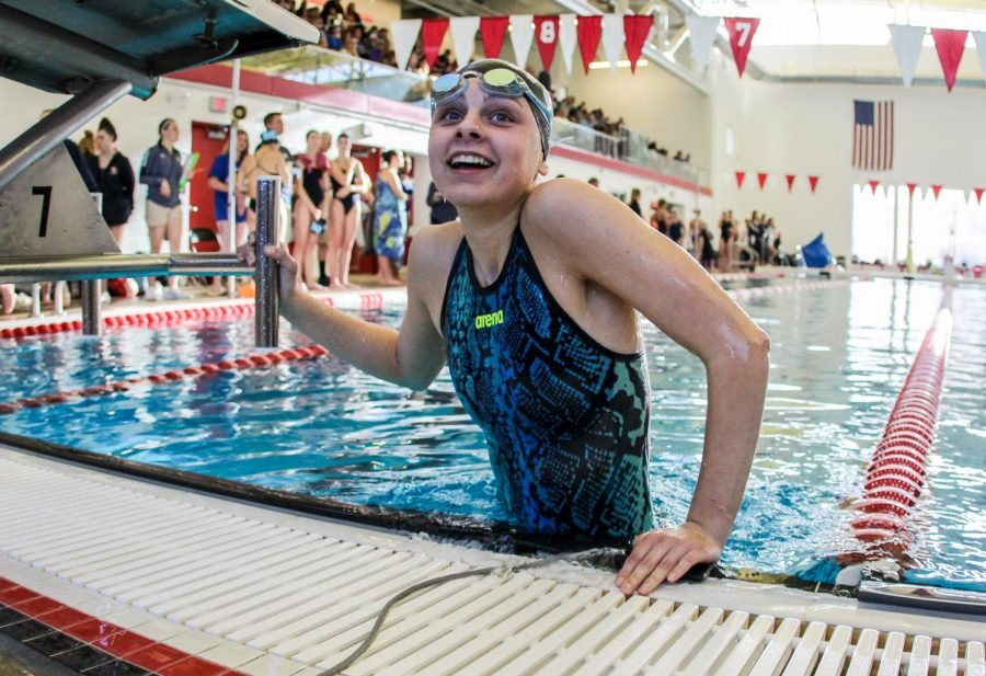 Climbing out of the pool, Sophie Howell, freshman, smiles after breaking her personal record in the 100 back at the Kirkwood invite Jan. 18.