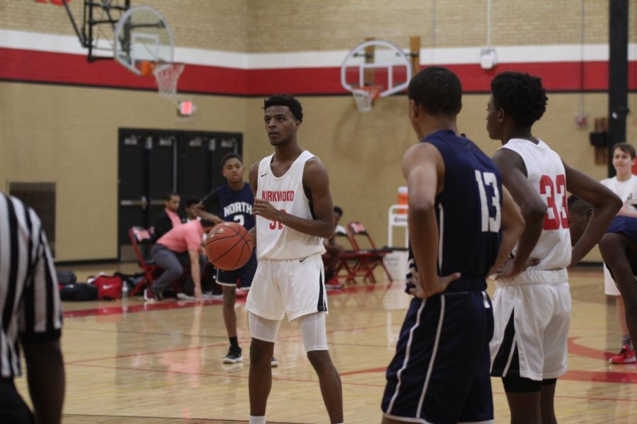 Before shooting a free throw, Kameron Richardson, freshman, holds the ball while surrounded by his teammates and opponents.