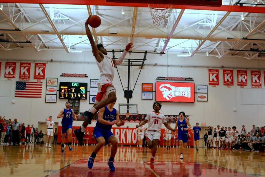 Jumping to lead the game, Will Lee, junior, dunks the ball as the Pioneers end the third quarter in a game against Ladue, Nov. 24.