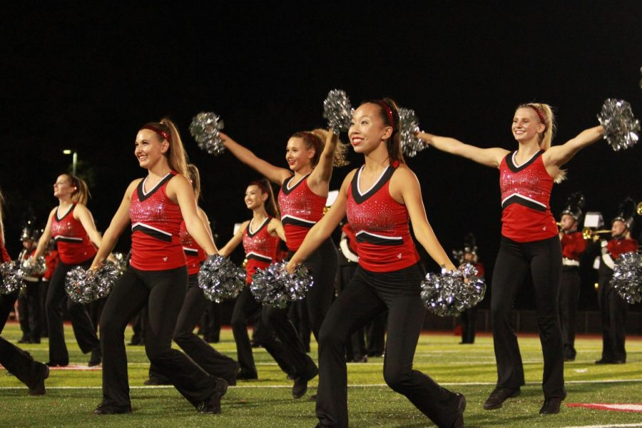 Senior Megan Cleveland smiles as she dances during the halftime performance of a varsity football game on Sept. 28