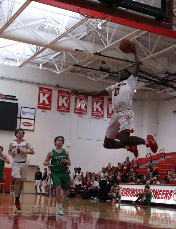 Jaylen Phipps, junior, jumps up for a dunk during the game against Marquette High School Jan. 21.