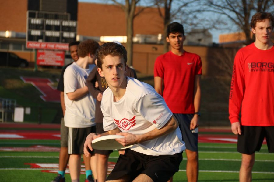 Looking downfield, Evan Dobson, senior, prepares to pass the disc to his teammate in warm-ups Jan. 14.