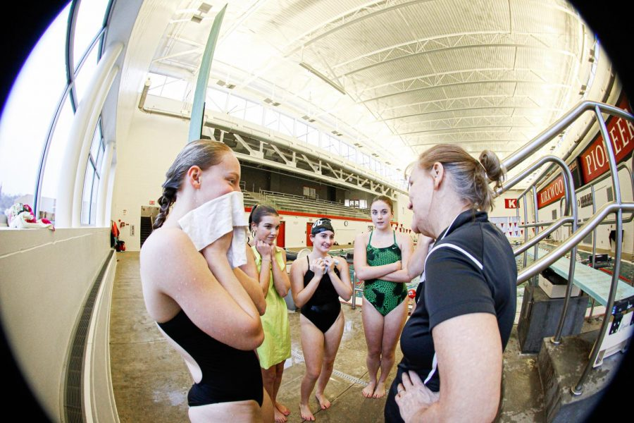 As she dries her face, Katie Hastings, junior, listens to her coach during practice Jan. 28.