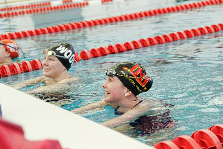 After finishing their laps, sophomore Alyssa Dennis and junior Julie Obertop, talk to their coach at the edge of the pool Jan 28.
